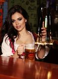 Beautiful sexy woman bartender posing in bar counter with beer. Fashion interior photo of beautiful sexy woman bartender posing in bar counter with glass of beer Stock Photo