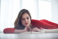 Fashion interior photo of beautiful sensual woman in elegant red dress lying on floor against big windows. Fashion interior photo of beautiful woman in elegant Stock Photography