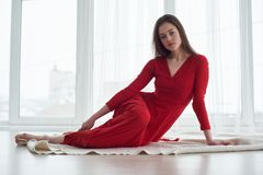 Fashion interior photo of beautiful sensual woman in elegant red dress lying on floor against big windows. Fashion interior photo of beautiful woman in elegant Stock Photo