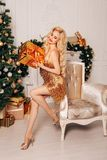 Beautiful woman with long blond hair in elegant dress posing near decorated Christmas tree royalty free stock image