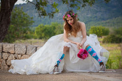Fashion jilted teen bride. Fashion jilted teen bride in wedding dress and sneakers Royalty Free Stock Image