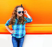 Fashion kid concept - portrait of stylish little girl child. Wearing a shirt and sunglasses posing against the colorful orange wall Royalty Free Stock Photography