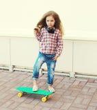 Fashion kid concept - stylish little girl child with skateboard Stock Photo