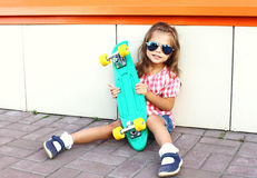 Fashion kid concept - stylish little girl child with skateboard wearing sunglasses in city Royalty Free Stock Photography