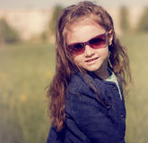Fashion kid girl posing in blue jacket and sun glasses on spring Stock Image