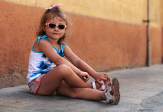 Fashion kid girl in sun glasses sitting on road near the wall Stock Photography