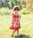 Fashion kid, little girl child wearing a dress. And red sunglasses outdoors in summer day royalty free stock images
