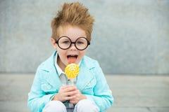 Fashion kid with lollipop near gray wall Stock Photo