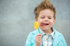 Fashion kid with lollipop near gray wall Royalty Free Stock Photo