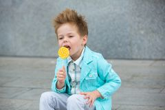 Fashion kid with lollipop near gray wall Royalty Free Stock Photos