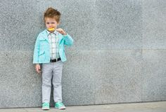 Fashion kid with lollipop near gray wall Royalty Free Stock Photography