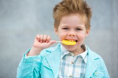 Fashion kid with lollipop near gray wall Royalty Free Stock Image