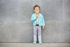 Fashion kid with lollipop near gray wall Royalty Free Stock Photos
