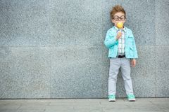 Fashion kid with lollipop near gray wall stock image