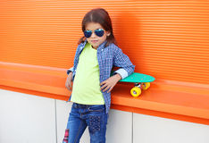 Fashion kid on skateboard wearing a sunglasses and checkered shirt over orange Stock Photos