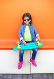 Fashion kid with skateboard wearing a sunglasses and checkered shirt over orange Royalty Free Stock Photography