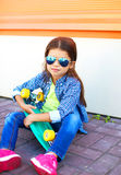 Fashion kid with skateboard wearing a sunglasses and checkered shirt over orange background Stock Image