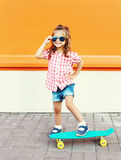 Fashion kid - smiling stylish little girl child with skateboard wearing sunglasses in city Royalty Free Stock Photography