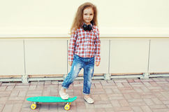Fashion kid. Stylish little girl child with skateboard. Having fun in the city royalty free stock images