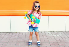 Fashion kid - stylish little girl child with skateboard wearing sunglasses in city Stock Photo