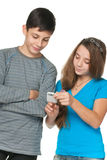 Fashion kids with a cell phone. A portrait of fashion kids with a cell phone; isolated on the white background Royalty Free Stock Photo