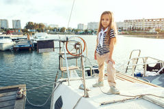 Fashion kids. Fashion child wearing navy clothes in marine style posing on white yacht in sea port stock photo