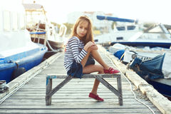 Fashion kids. Fashion child wearing navy clothes in marine style posing on wooden berth in sea port royalty free stock image