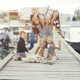 Fashion kids. Many fashion kids wearing navy clothes in marine style walking in the sea port and holding hands Stock Photo