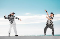 Fashion kids pointing on copy space over sky background. Stock Photos