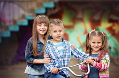Fashion kids. Portrait of happy fashion little kids having fun by painted wall Stock Images