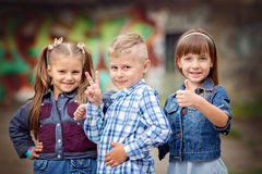 Fashion kids. Portrait of happy fashion little kids having fun by painted wall Royalty Free Stock Photography