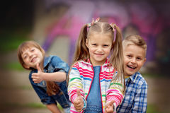 Fashion kids. Portrait of happy fashion little kids having fun by painted wall Royalty Free Stock Photo