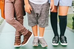 Fashion kids shoes. Fashion shoes on kids. Three pairs of children`s feet wearing comfortable and fashion trainers. Back to school concept stock image