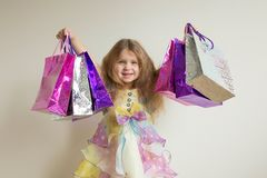Fashion kids shopping. Beautiful smiling little girl. With shopping bags and gifts. Happy child holds a lot of gifts. Sale, holidays, fashion, shopping concept Royalty Free Stock Images