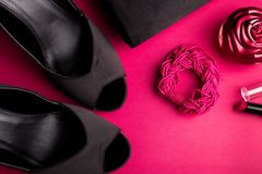 Fashion Lady Accessories Set. Black and pink. Minimal. Black Shoes, bracelet, perfume, lipstick and bag on pink background. Flat l. Ay Royalty Free Stock Photography