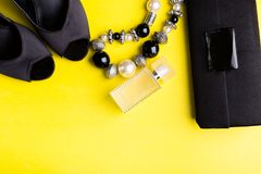 Fashion Lady Accessories Set. Black and yellow. Minimal. Black Shoes, bracelet, perfume and bag on yellow background. Flat lay. Fashion Lady Accessories Set Stock Photography