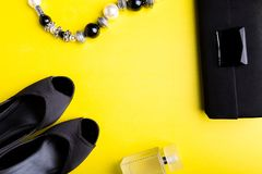 Fashion Lady Accessories Set. Black and yellow. Minimal. Black Shoes, bracelet, perfume and bag on yellow background. Flat lay. Fashion Lady Accessories Set Stock Photos