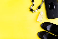 Fashion Lady Accessories Set. Black and yellow. Minimal. Black Shoes, bracelet, perfume and bag on yellow background. Flat lay. Fashion Lady Accessories Set Stock Image