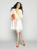 Fashion lady. Beautiful brunette model in fashion clothes posing in studio. Wearing coat, handbag, red shoes Royalty Free Stock Photos