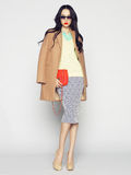 Fashion lady. Beautiful brunette model in fashion clothes posing in studio. Wearing coat, handbag, shoes Stock Photography