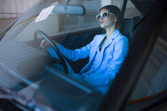 Fashion lady driving a car in a blue suit. Stylish girl sitting in the car and holding steering wheel. Woman in the car on the parking Royalty Free Stock Image