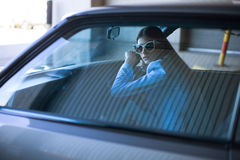 Fashion lady driving a car in a blue suit. Stylish girl sitting in the car and lying on the steering whee. L. Woman in the car on the parking Royalty Free Stock Photo