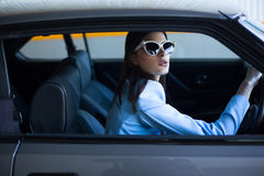 Fashion lady driving a car in a blue suit. Stylish girl sitting in the car and holding steering wheel. Shot through the side window. Woman in the car on the Stock Image