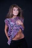 Fashion lady pulling the shirt and uncover her belly. Sweet girl with straight hair and purple shirt posing in studio. She pulling the shirt and  uncover her Royalty Free Stock Image