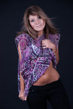 Fashion lady pulling the shirt and uncover her belly. Sweet girl with straight hair and purple shirt posing in studio. She pulling the shirt and  uncover her Stock Image