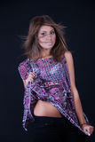 Fashion lady pulling the shirt and uncover her belly. Sweet girl with straight hair and purple shirt posing in studio. She pulling the shirt and  uncover her Stock Images