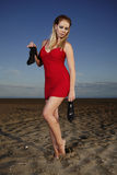 Fashion lady in red dress on the beach. Young and nice lady posing on the sand beach for fashion book photos in Italian resort Caorle royalty free stock image