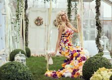 Fashion lady in spring scenery wearing flower dress. And posing on swing royalty free stock photos