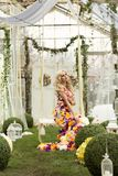 Fashion lady in spring scenery wearing flower dress. And posing on swing stock photo