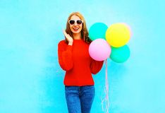 Fashion laughs woman holds a colorful air balloons on blue. Background Stock Image
